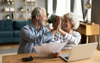 Smiling couple look at heating and cooling bill